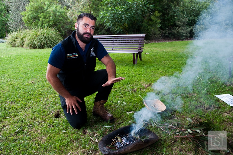Guide Charles Soloman starts the Aboriginal Heritage Walk at Royal Botanic Gardens in Melbourne with a smoking ceremony