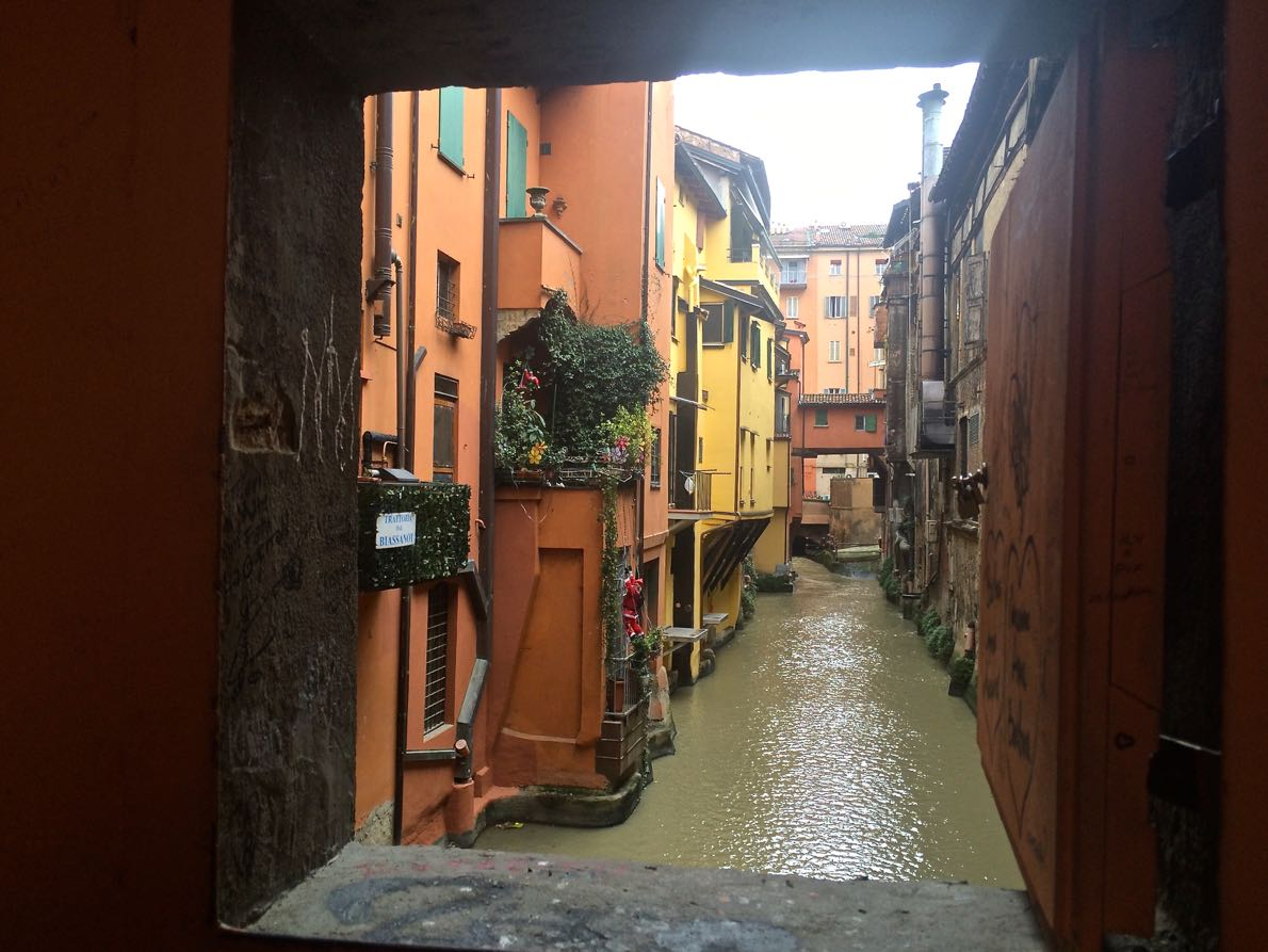 Through the wall - a view of Bologna's canals through the wall of one of its streets