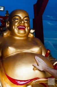 Rubbing the tummy of the golden Buddha at Puh Toh Tze Chinese temple