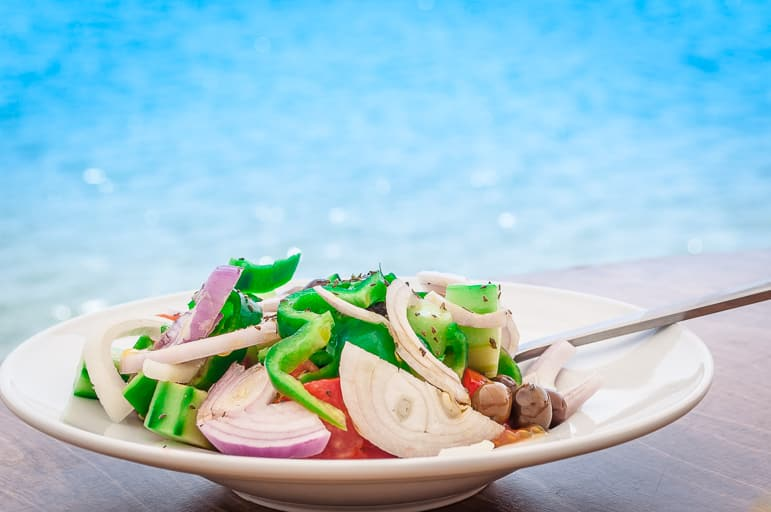 Greek cuisine - a Greek salad against the sea off the Peleponnese, Greece