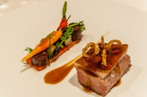 Roasted saddle of lamb, bell peppers, young vegetables and confit sausage
