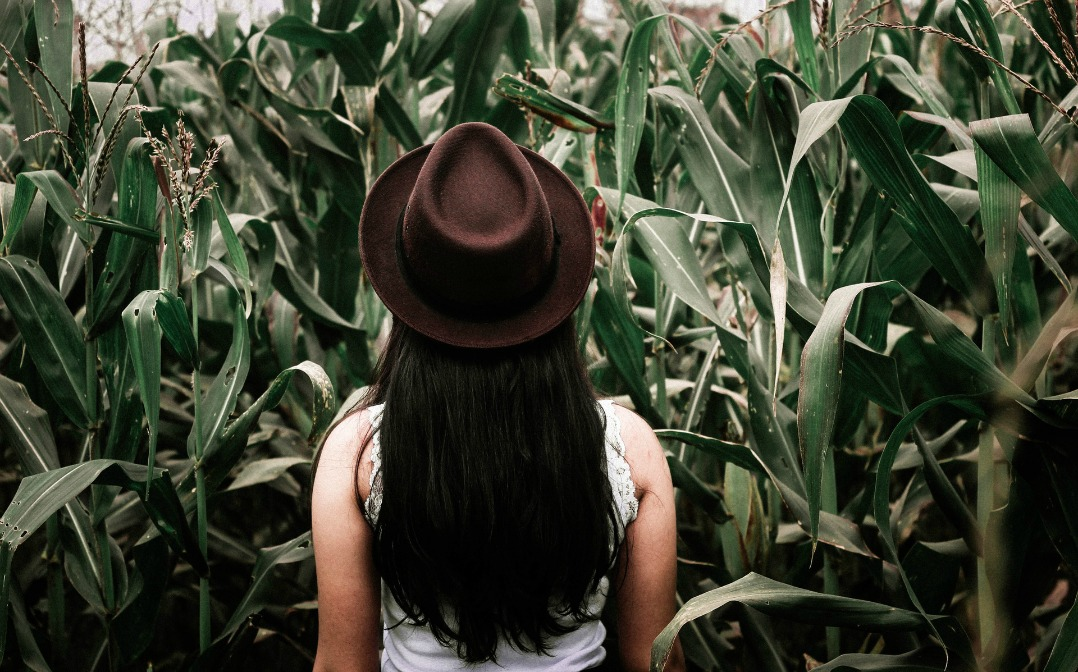 Solo female travel - woman with hat looking at grass