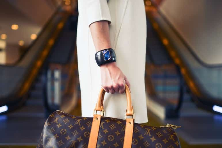 travel beauty - woman carrying louis vuitton luggage at airport