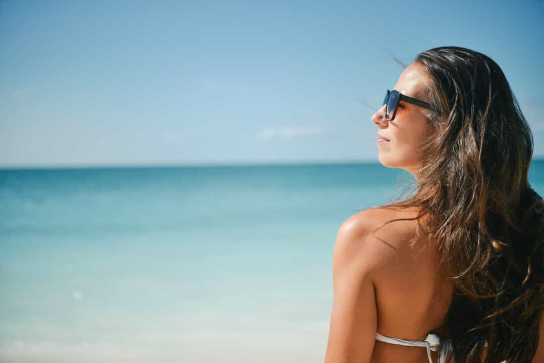 travel beauty - woman on beach with sunglasses on in bikini