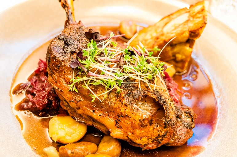 Crispy duck haunch with apple red cabbage, with caramelised chestnut and pretzel slice