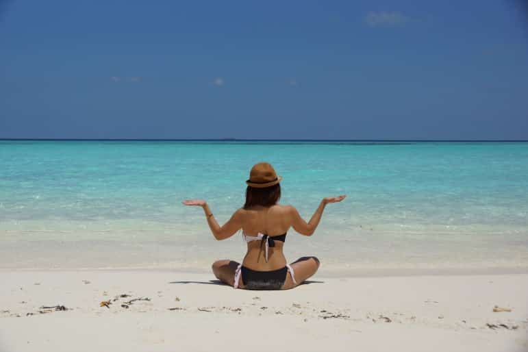 Spa treatments - woman on beach in yoga pose